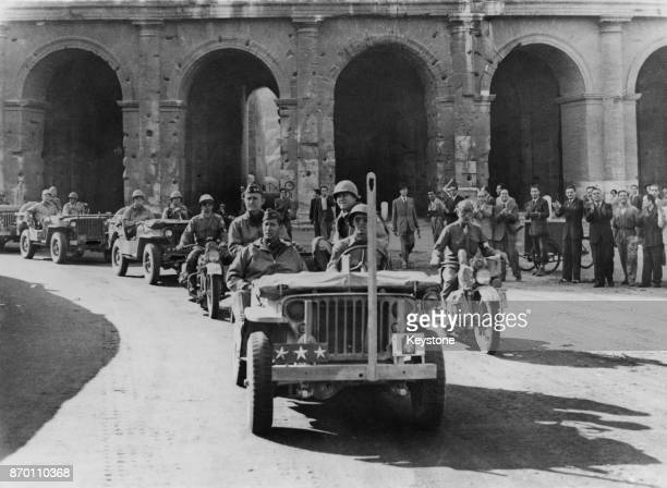 Lieutenant General Mark W Clark commander of the United States Fifth Army passes the ancient Coliseum in Rome Italy after capturing the city during...