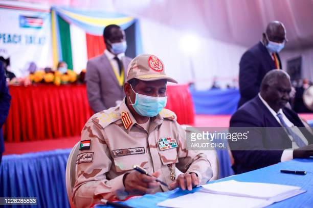 Lieutenant general Mohamed Hamdan Dagalo of Sudan signing the peace deal document between the government and the rebel groups during the singing of...