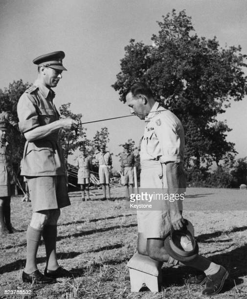 Lieutenant General Sir Oliver Leese of the British Army receives a knighthood from King George VI during the King's visit with the Eighth Army in...