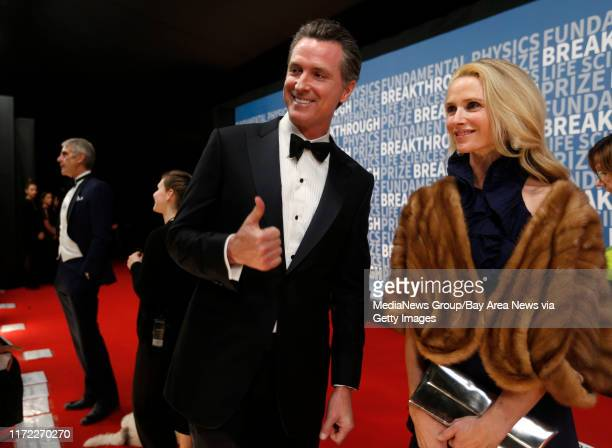 Lieutenant Governor Gavin Newsom gives a thumbs up while walking on the red carpet with this wife Jennifer before the Breakthrough Prize ceremony at...