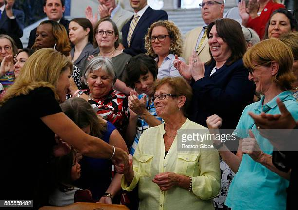 Lieutenant Governor Karyn Polito left reaches over to shake hands with Dorothy Simonelli an Everett Lunch Lady who fought for equal pay decades ago...