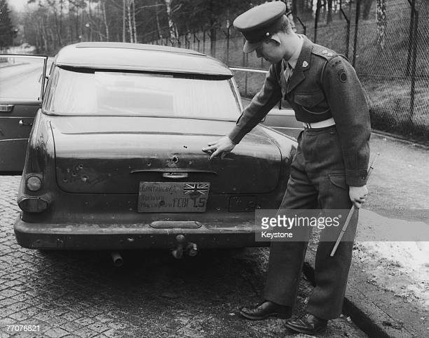 Lieutenant Hard of the Royal Military Police inspects the bulletholes in a car belonging to the British Military Mission in Potsdam at the British...