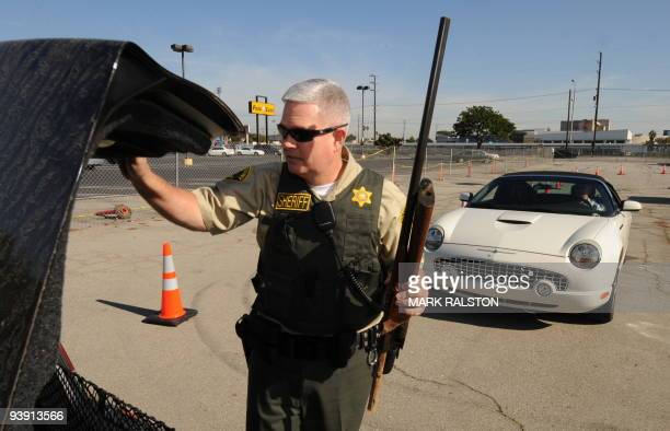 Lieutenant Jeff Adams from the Sheriff's Department's Lennox Station in South Central Los Angeles retrieves a rifle from a persons car during a 'Gun...