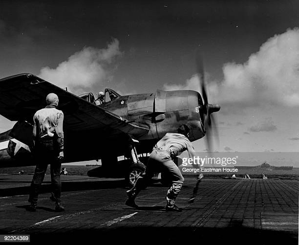 Lieutenant John M Clark waves the takeoff flag for a Grumman F6F3 Hellcat of Fighting Squadron Sixteen on the deck of the aircraft carrier USS...