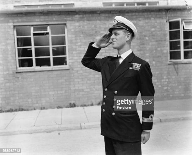 Lieutenant Philip Mountbatten, prior to his marriage to Princess Elizabeth, saluting as he resumes his attendance at the Royal Naval Officers School...