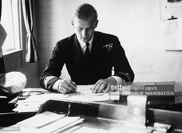 Lieutenant Philip Mountbatten prior to his marriage to Princess Elizabeth working at his desk after returning to his Royal Navy duties at the Petty...