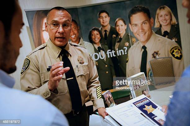 Lieutenant Ray Baez an officer with the California Department of Corrections and Rehabilitation speaks with job seekers at the Career Choice Inland...