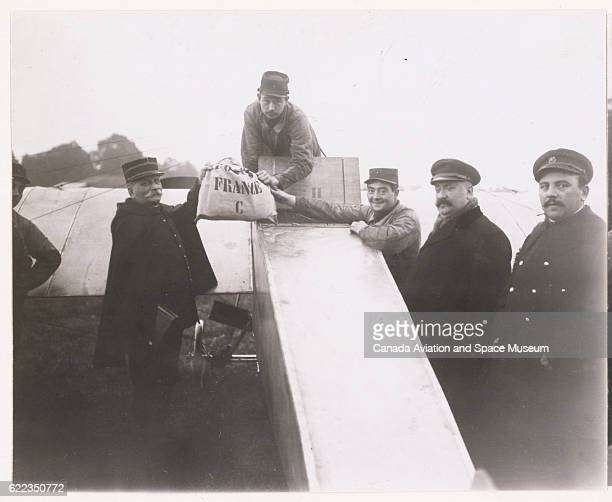 Lieutenant Ronin the Minister of Commerce and others gather for an experimental airmail delivery in 1913 using a military monoplane aircraft designed...