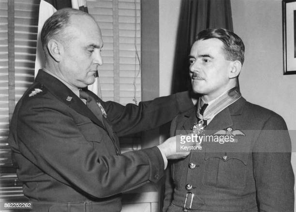 LieutenantGeneral Ira C Eaker Deputy Commander of the Army Air Forces and Chief of Air Staff of the American Air Force presents the Legion of Merit...
