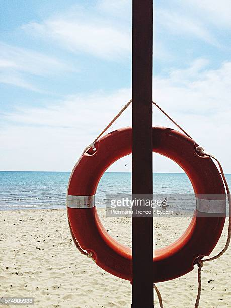 Life Belt Hanging On Pole Against Sky At Beach