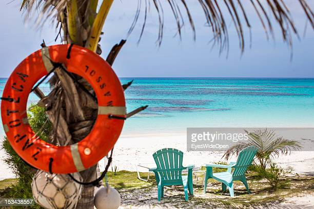 A life belt lifesaver is hanging on a palmtree at the white and sandy 8MilesBeach with two chairs overlooking the turquois blue waters of the...