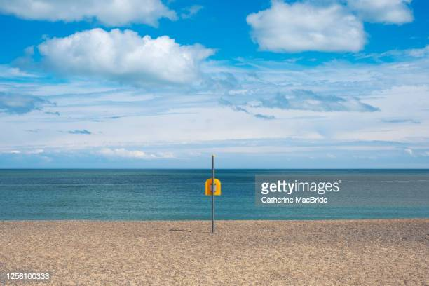 life bouy on empty beach on irelands east coast - catherine macbride stock pictures, royalty-free photos & images
