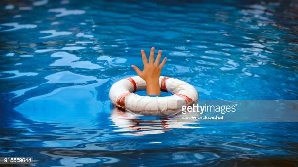 Life Buoy and The woman's hand in swimming pool .Background for rescue concept .