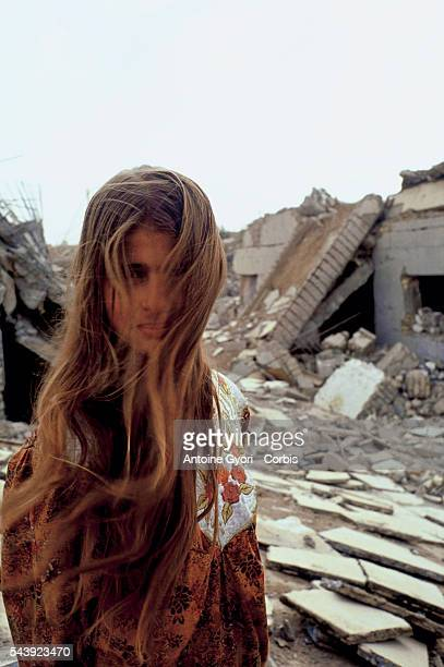 Life Continues in Saddam City Eightyearold Warda stands in front of the ruins of her house in Saddam City