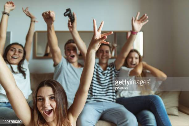 life during covid-19 pandemic lockdown: group of friends quarantine at home, watching sport on tv - world sports championship stock pictures, royalty-free photos & images