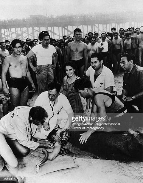 A life guard and a doctor attempt to save a swimmers life on Coney Island Beach New York 1940 A woman oblivious to the trauma smiles at the camera...