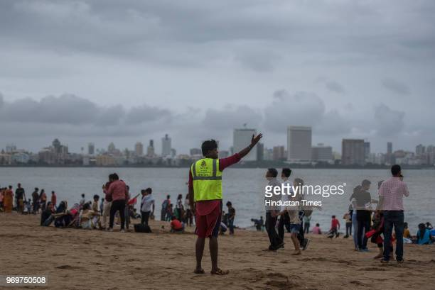 Life guard gives warning to the people to come out from the water as hightailed approaches at Girgaon chowpatty on June 7 2018 in Mumbai India Heavy...