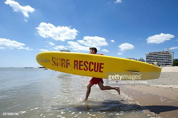 A life guard runs into the sea with a surfboard on at a beach in SaintNazaire western France on July 10 2014 during the first week of the French...