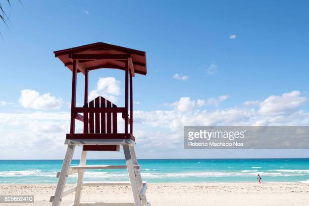 Life Guard seat or hut on deserted white sand beach on a sunny day with clouds gathered at horizon