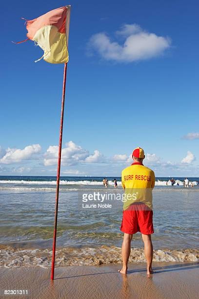 Life guard standing next to flag