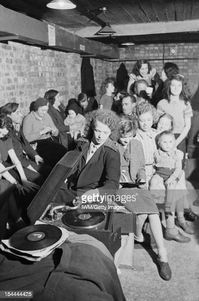 Life In An Air Raid Shelter North London England A young woman places the gramophone needle on a record to bring some light relief to an air raid...