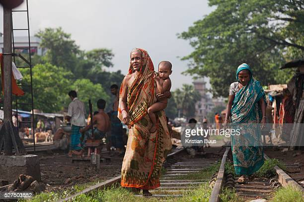 Life in the slums by the railway tracks in TejgaonThe grand mother of Sumi walking along the tracks with her grand child child of Sumi's father and...
