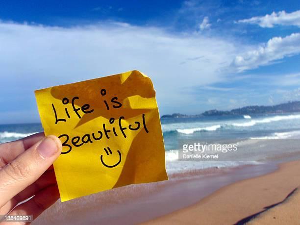'Life is beautiful' written on yellow sticky note