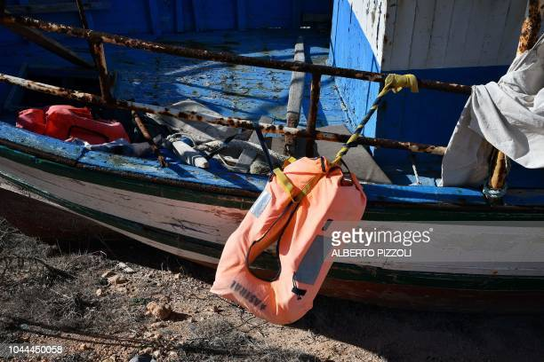 A life jacket from Spanish NGO Astral is attached to a boast in the socalled boat cemetery where skiffs are dumped after the migrants and refugees'...