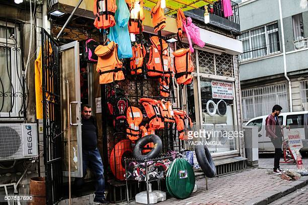 TOPSHOT Life jackets inner tubes of tires and woolie hats are on sale at a store in Kumkapi district of Istanbul on February 1 2016 At least 37...