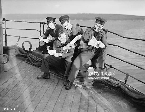Life On Board HMS Dunluce Castle, Home Fleetanchorage, December 1941, Crew men enjoying their Christmas mail on the deck of HMS DUNLUCE CASTLE.