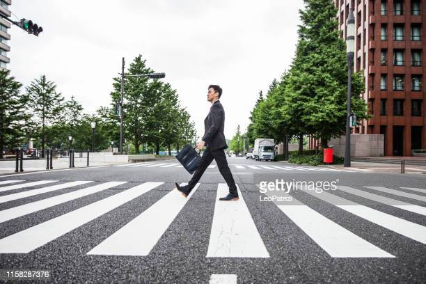 life on the go in the business district. japanese businessman in tokyo financial district - zebra crossing stock pictures, royalty-free photos & images
