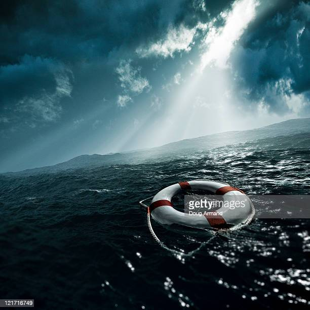 life preserver afloat on stormy seas - rescue stock pictures, royalty-free photos & images