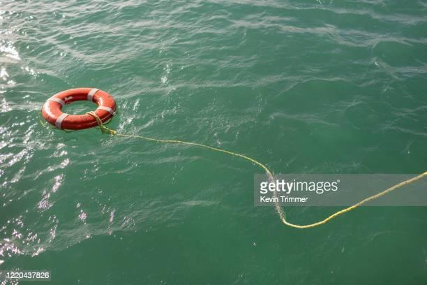 life preserver floating in ocean water - sos ストックフォトと画像