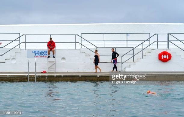 A life quard watches customers swimming again at Jubilee Pool openair seawater lido on the morning it reopened to the public once again after the...