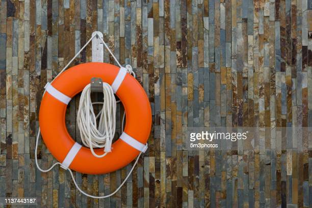 life ring buoy lifesaver on textured wall - lifeguard stock pictures, royalty-free photos & images