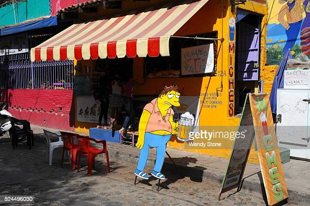 Life size cardboard cutout of Barney Grumble from the Simpsons holding a beer mug in front of a snack bar in Ajijic Mexico