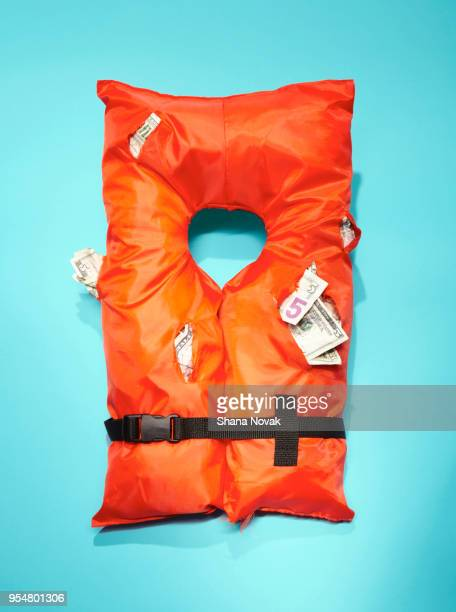 life vest stuffed with money - protection stock pictures, royalty-free photos & images