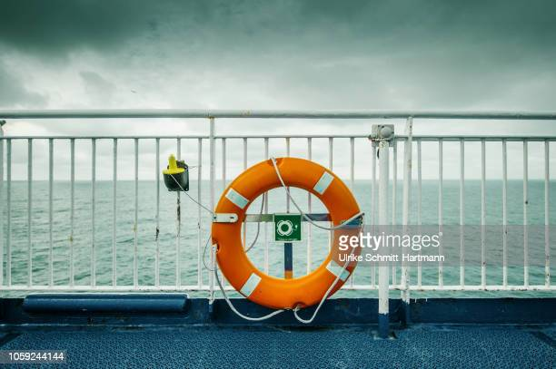 lifebelt fixed at ship's railing on a cloudy day - ponte di una nave foto e immagini stock