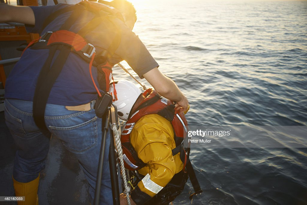 Lifeboat crew training and pulling up team member from sea : Stock Photo