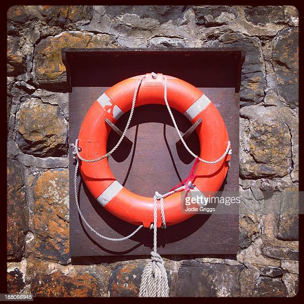 Lifebuoy ring hanging on stone wall of jetty