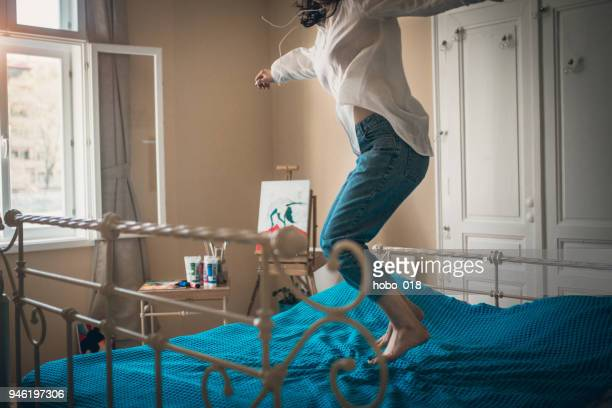 Lifeful woman jumping on bed