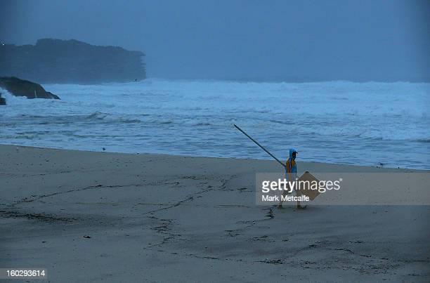 A lifeguard at Bronte walks onto the beach at first light to erect a beach closed sign after winds and rain battered Sydney last night on January 29...