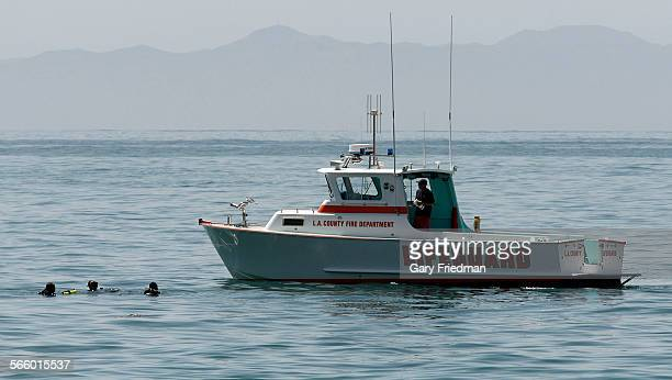 A lifeguard boat from the LACounty Fire Department approaches three divers in the ocean hundreds of yards off the coast near the Terranea Resort on...