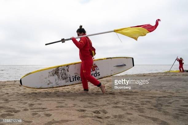 Lifeguard carries a paddle board and flag along the beach in Skegness, U.K., on Monday, May 31, 2021. U.K. Health Secretary Matt Hancock said people...