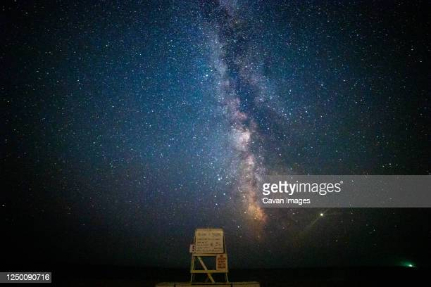 lifeguard chair under the milky way night sky on the beach. - massachusetts stock pictures, royalty-free photos & images