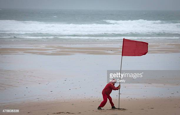 RNLI lifeguard erects a red warning flag ahead of a practice for the annual beach polo competition being held on the beach at Watergate Bay near...