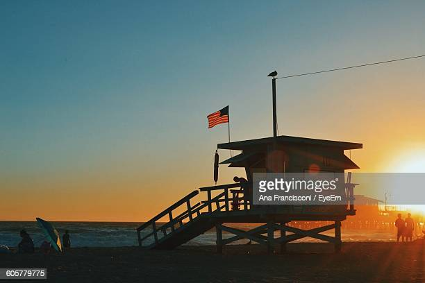 Lifeguard Hut At Sea Shore Against Clear Sky During Sunset