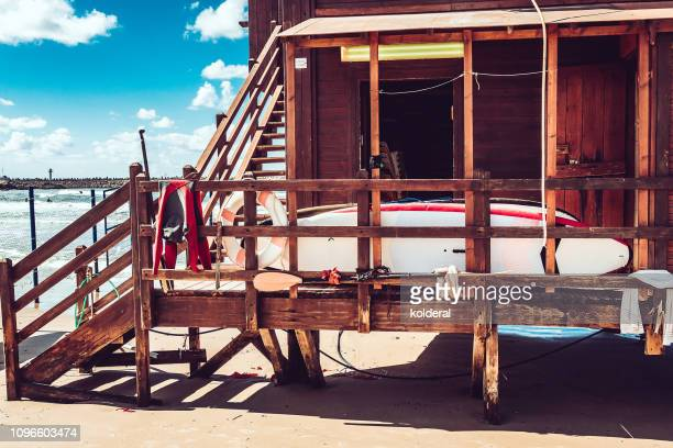 lifeguard hut with surfboard against blue sky on mediterranean beach - shack stock pictures, royalty-free photos & images