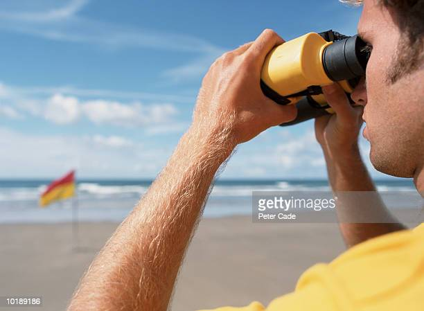 lifeguard keeping watch on beach - lifeguard stock pictures, royalty-free photos & images
