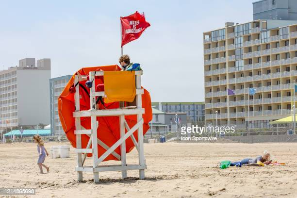 A lifeguard keeps a watchful eye on a child playing in the sand as an adult relaxes to kick off Memorial Day weekend A red flag is flown to indicate...